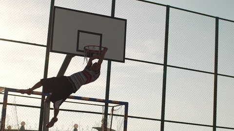 Caucasian male player in streetball doing two-handed slam dunk on outdoor sports ground in slowmotion