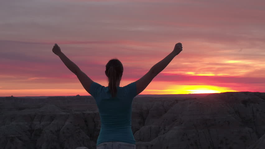 SLOW MOTION CLOSE UP: Young woman celebrating and proudly outstretching her arms towards pink sky at stunning sunset. Happy hiker successfully rising hands up and enjoying the moment at red sunrise #27710536