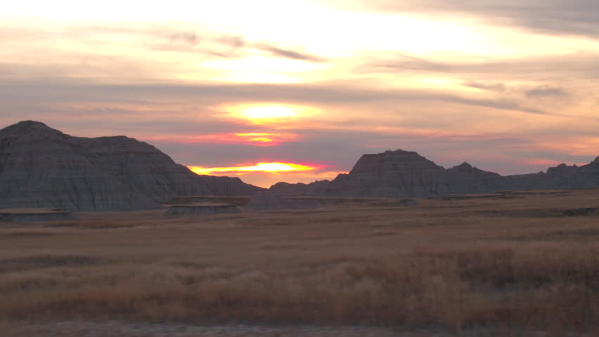 AERIAL: Beautiful endless sandstone formations and dry grass prairie at Badlands National Park at sunset. Amazing landscape with eroded rocky mountains rising out of vast grassland at reddish sunrise