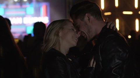 Man hugging and kissing girlfriend at night club, couple enjoying concert