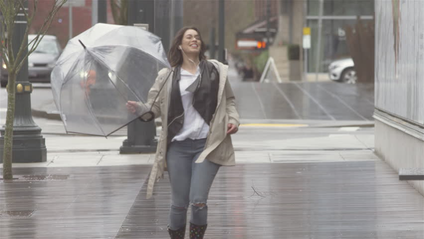 Young beautiful Latin woman dancing around with an umbrella in the city while listening to music