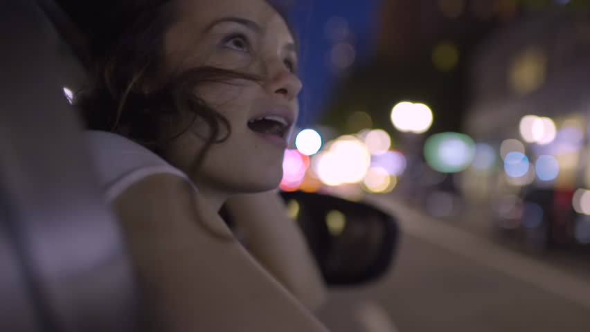 Happy Young Woman Leans Out Passenger Side Car Window, She Looks In Wonder And Awe At All The Beautiful Sights Of The City (Slow Motion) | Shutterstock Video #27728296