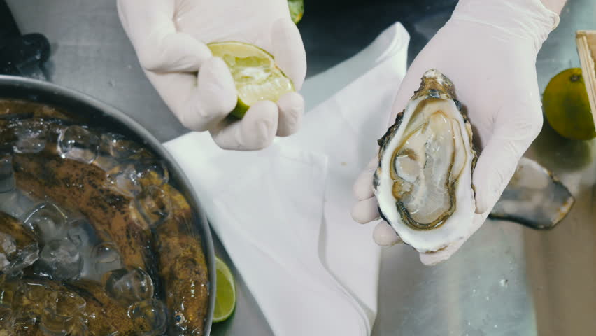 Cook pours the oyster with fresh lemon juice