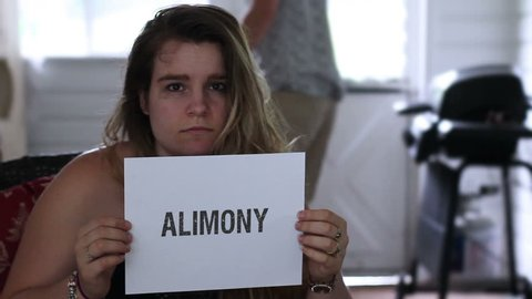 Frustrated ex wife holding up an alimony sigh with angry husband in background