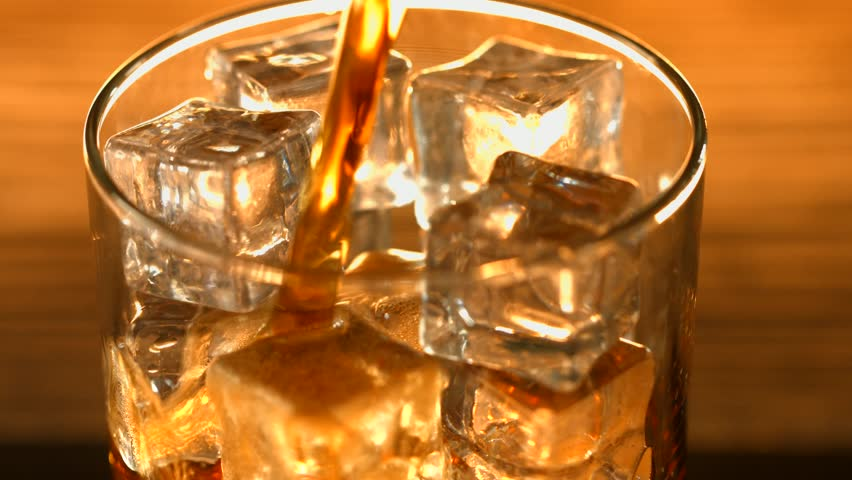 Cola pouring in glass with ice cubes over wooden table background. Cola with Ice and bubbles in glass. Soda closeup. Food background. Close-up. 4K UHD video footage. Ultra high definition 3840X2160p