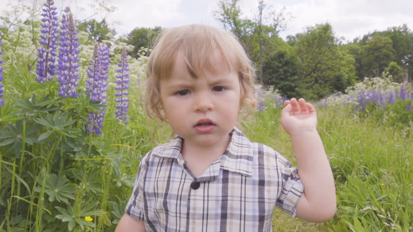 Angry little boy hands bangs the camera in the park looking at camera. Slow motion