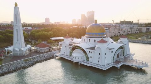 Aerial Footage - Dawn at a mosque, The Melaka Straits Mosque, located on the man-made Malacca Island near Melaka City, Melaka, Malaysia. Color corrected with film look color LUT. Moody exposure.
