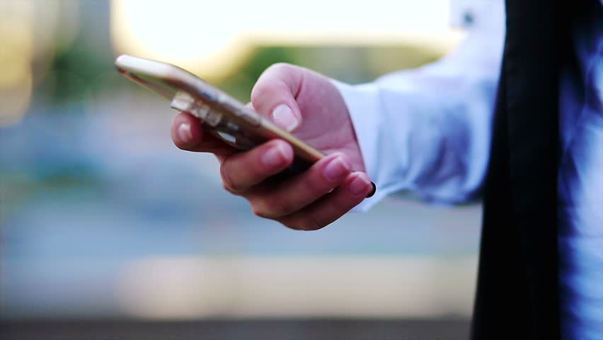Closeup of woman's hands browsing mobilephone with a cityscape at the background | Shutterstock HD Video #27815377