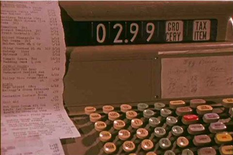1970s: A grocery store cashier types the costs of different items into a cash register in 1971.