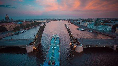 Aerial shot of the ship sails through raised Palace Bridge in Neva river, St. Petersburg, Russia
