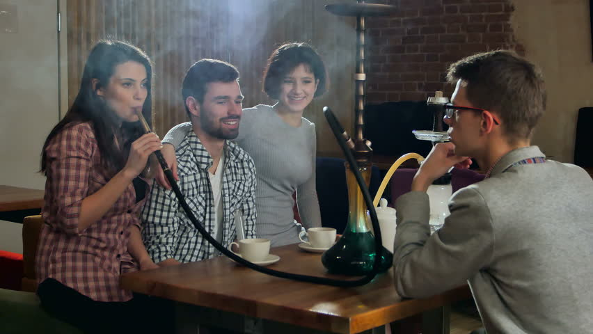 Young friends smoking hookah in shisha cafe