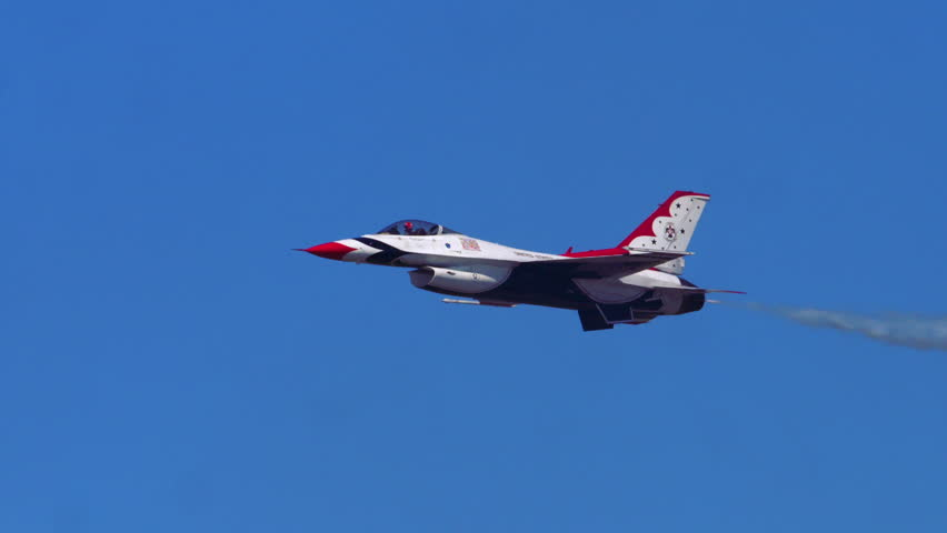 TITUSVILLE, FLORIDA - CIRCA MARCH 2017: USAF Thunderbirds Demonstration Team performs at airshow - single F18 flying past camera and rolls over on side to show top of plane in super slow motion