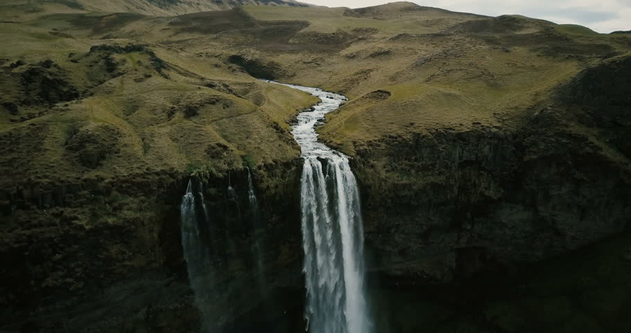 Aerial view to the mountains river flows through the valley and falls down. Waterfall Seljalandsfoss in Iceland. #27878341