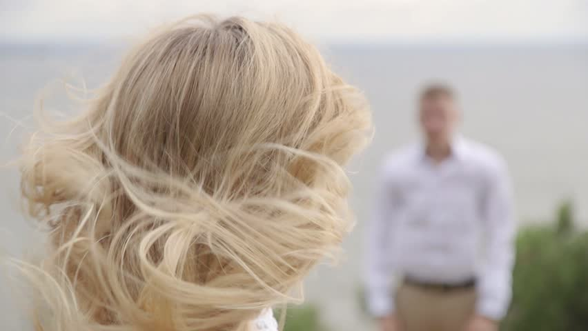 The woman in white dress looking at her boyfriend on the edge of the cliff. View of the ocean. Hair fluttering in the wind #27879136