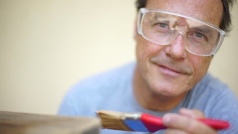 Good-looking man carpenter with goggles painting with varnish a wooden table to renovate it. Looking at camera and smiling.