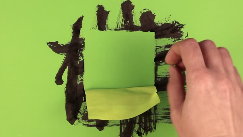 The hand tears off the sticker. The green background is stained with ink.