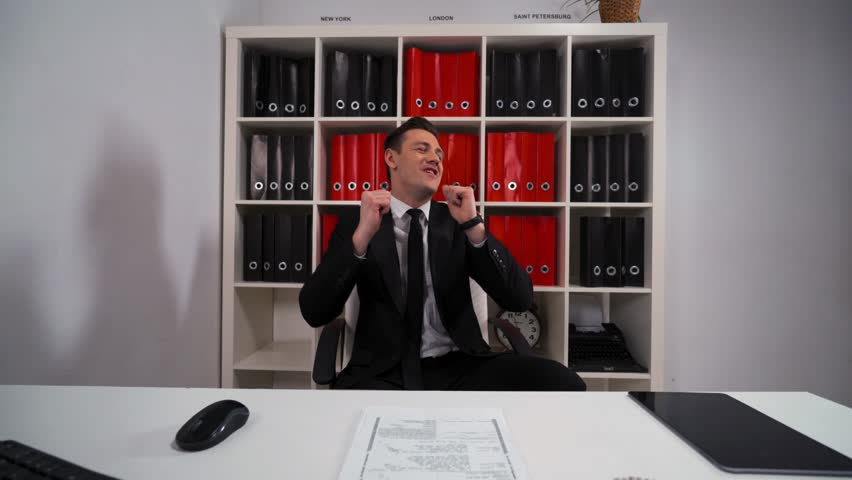 4k POV. Young attractive Handsome businessman funny dancing in office armchair necktie. He strip remove his black suit. Computer, mouse, keyboard, digital pad, shelf with folders. Wide shot.