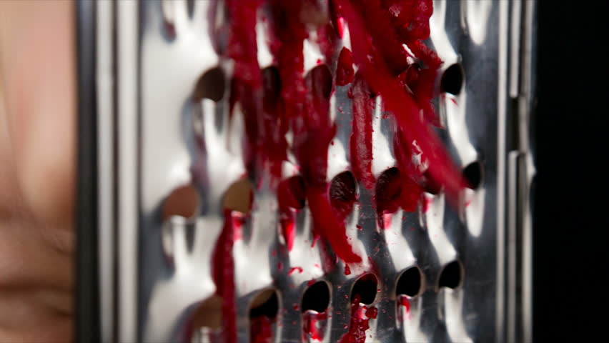 Rubbing the beetroot on metal grater, slow motion, closeup