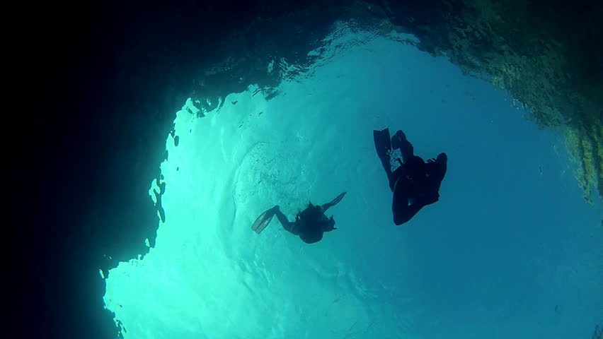 Blue diver silhouettes.     Father and daughter diving.     Shutterstock HD Video #2793886