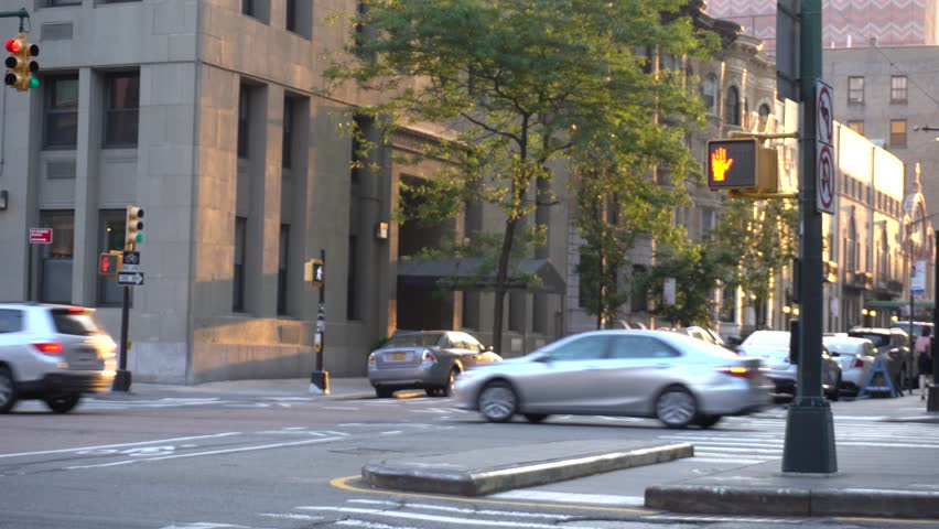 View of a typical New York City downtown intersection during golden hour evening. Brooklyn street view cars cross road