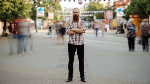 Timelapse of Young bearded man standing still at sidewalk in crowd traffic stream with people moving fast
