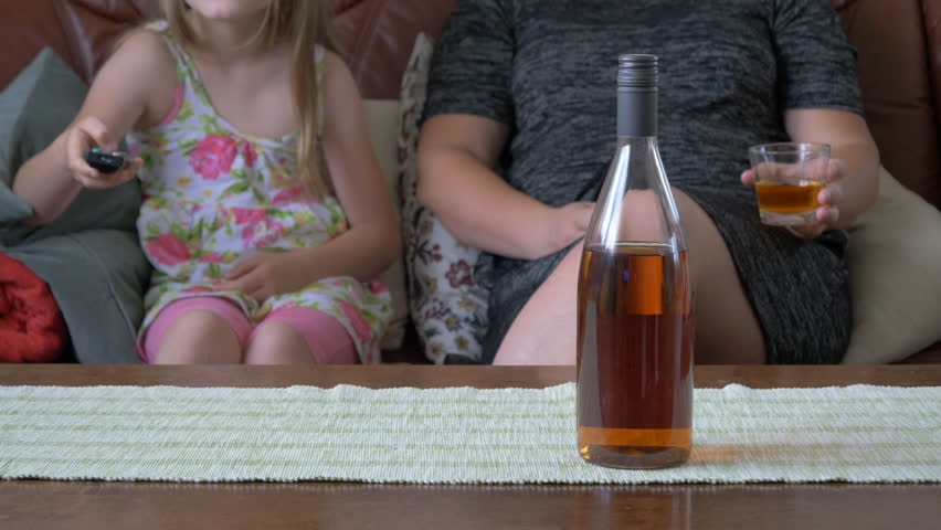 Mother drinks alcohol in front of a child. Pathological family. | Shutterstock HD Video #27993808