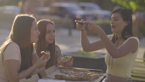 Carefree Hispanic Young Woman Tries To Take A Photo Of Pizza, Almost Drops The Phone On The Pizza, Funny/Everyone Laughs