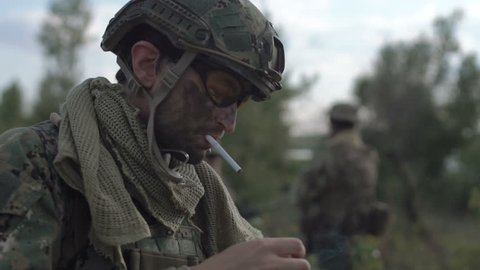 Slow motion, close view soldier on battlefield having a smoke while other soldiers talking at background