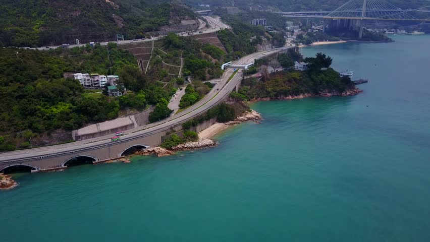 Large highway, Castle Road at shore of mount bottom, newest Tuen Mun Rd bend up on slope, aerial shot. Little beach stripe, Gemini Point cape with Airport Core Programme Exhibition Centre | Shutterstock HD Video #28028326