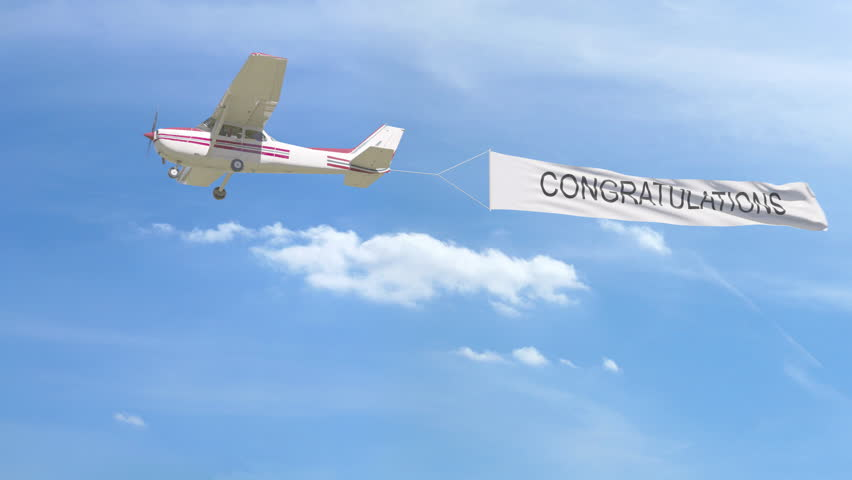 Small propeller airplane towing banner with CONGRATULATIONS caption in the sky