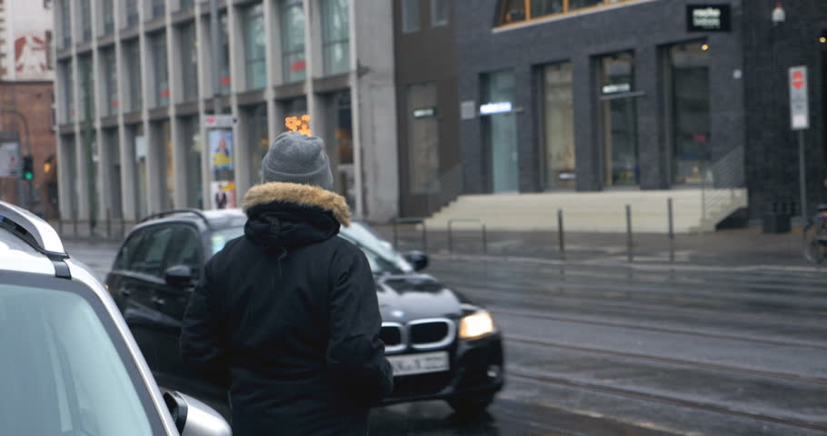 A young man turns around and gives a thumbs up and a smile to the cameraman while waiting to cross the street. The weather outside is rainy and damp.  | Shutterstock HD Video #28047004
