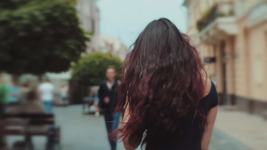 Back view of attractive long-haired curly brunette woman walking down the city-street or alley, turns to camera and gives a beautiful smile, wind plays with her hair. Urban settings on the background.