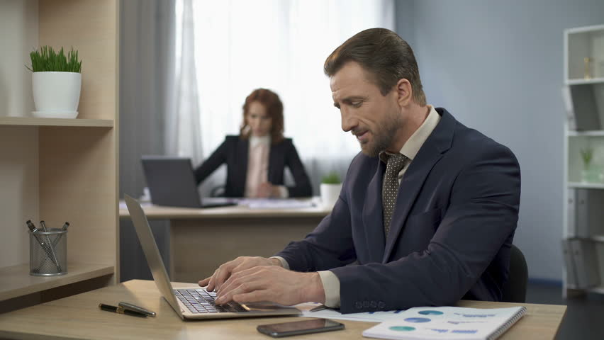 Man finishing typing on laptop, sitting content at desk, exceeded expectations | Shutterstock HD Video #28054516