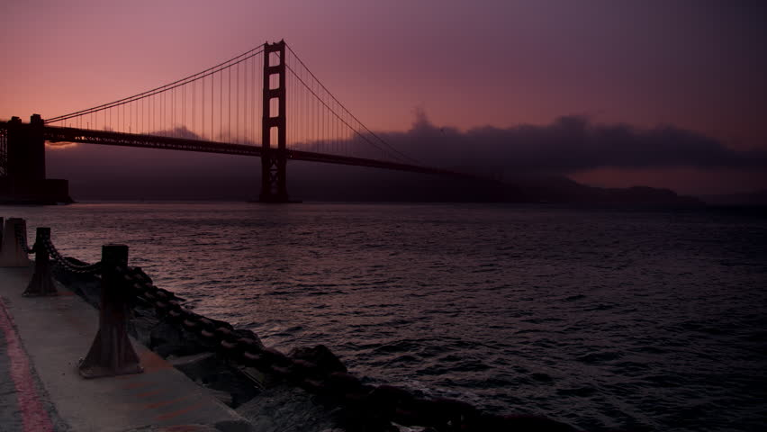 Foggy clouds rolling past Golden Gate Bridge at sunset with dark clouds over the water.