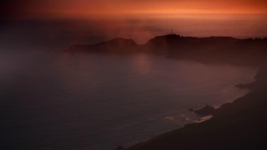 Foggy ocean shoreline at sunset