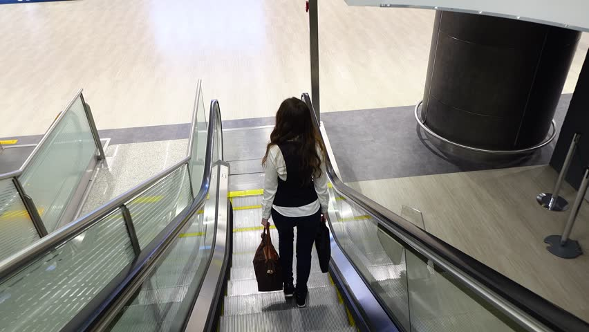 Informal Dressed Woman Come Out From Moving Staircase, POV Back Top Camera  Follow Lady.