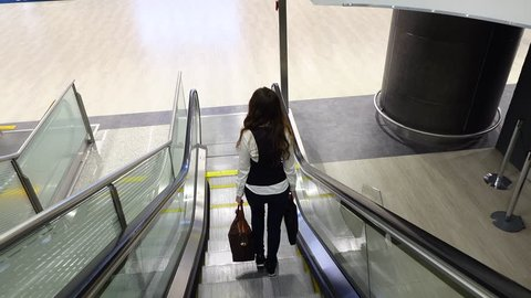 Informal dressed woman come out from moving staircase, POV back top camera follow lady. Bright modern interior, transportation hub passage