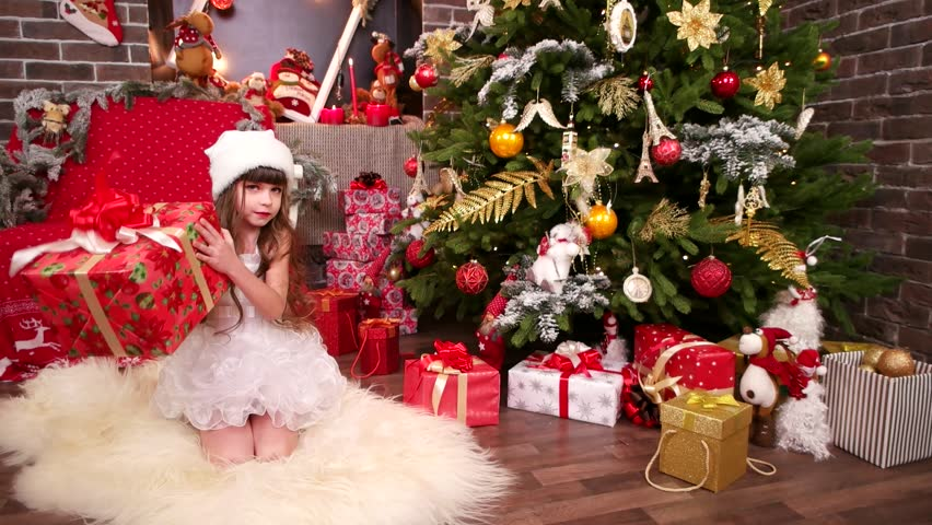 years gifts under christmas tree for younger sister presents from santa claus for daughter close up of little girl with christmas gifts happy winter