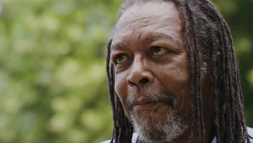 Mature Jamaican man talking during a game of chess, in slow motion