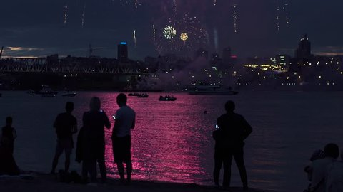 people silhouettes on a background of fireworks. group of people enjoying the city night view and fireworks