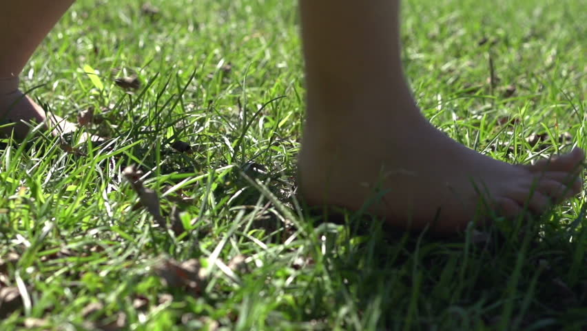 Child feet run by in grass slow motion