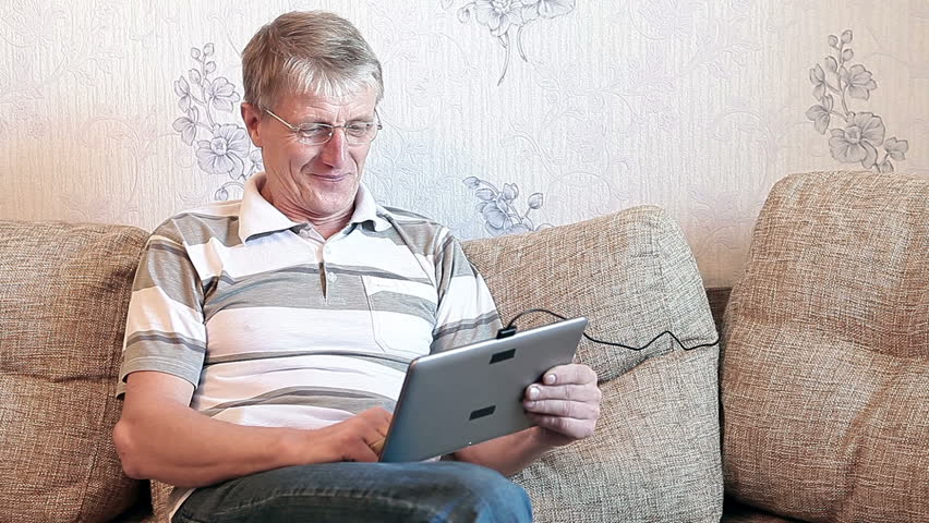 Senior adult Caucasian man interested with a new tablet pc, sitting on sofa in domestic room