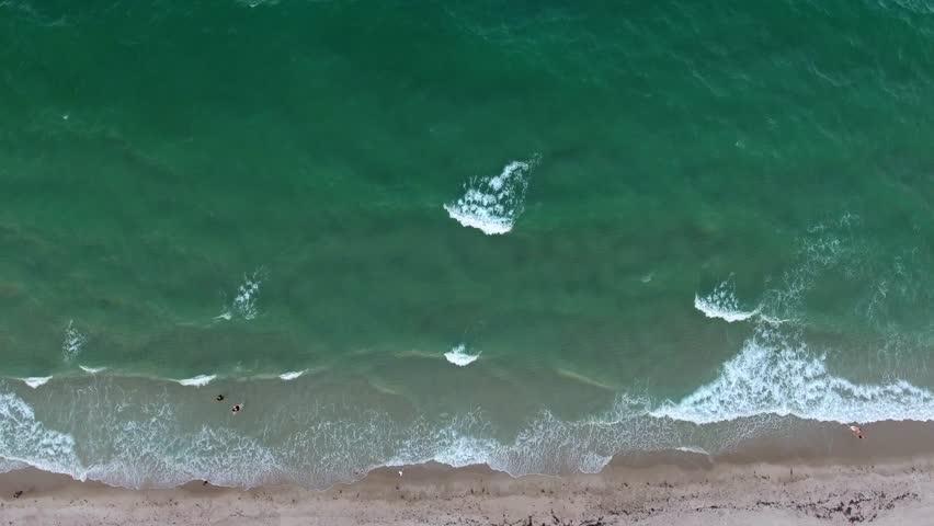 Tropical beach ocean video loop with seamless never ending footage showing aerial bird eye view of green foaming ocean waves breaking against sandy coast line and overhead people in playing water | Shutterstock HD Video #28174816
