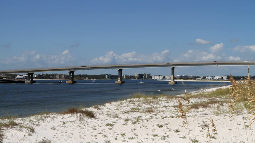 Traffic moves across the inter-coastal waterway on route 98 bridge at Perdido Pass with dunes and sea oats in the foreground and condominiums in the background all part of Orange Beach, Alabama.