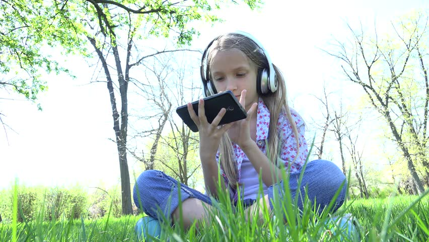Child Playing Tablet in Park, Girl with Headphones on Grass Outdoor in Summer 4K | Shutterstock HD Video #28194778
