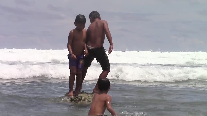 SULANGAN, PHILIPPINES - CIRCA MARCH 2017:  Filipino kids play and bathe on a beach on the ocean near the village of Sulangan, Eastern Samar, Philippines.