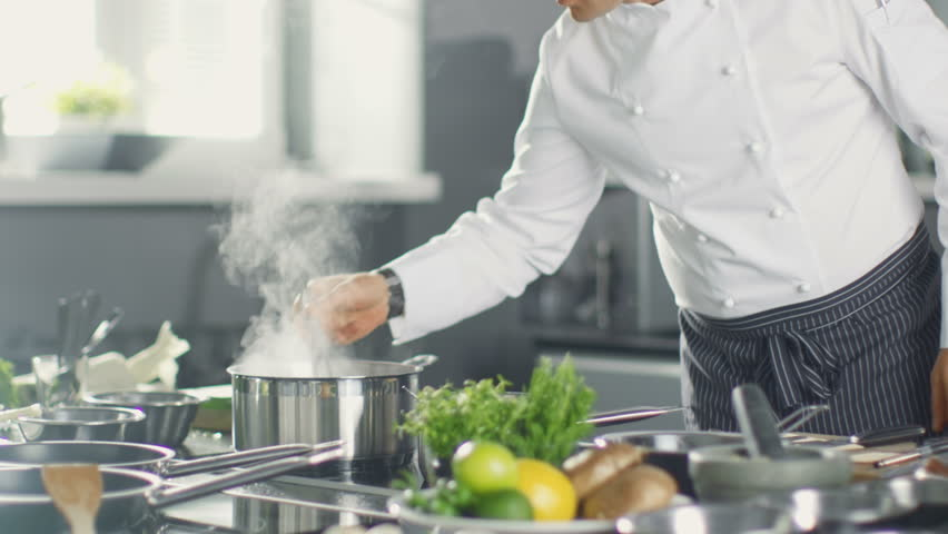 Famous Restaurant Chef Stirs Soup or Sauce in a Saucepan. His Preparing Dishes in Modern Kitchen.  Shot on RED EPIC-W 8K Helium Cinema Camera.