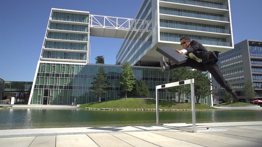 young businessman with briefcase running over hurdle in slow motion