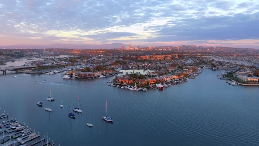 Aerial sunset shot with a drone over Newport Beach harbor with Linda Isle island, Pacific Coast Highway or PCH and Fashion Island in the background with pink skies.