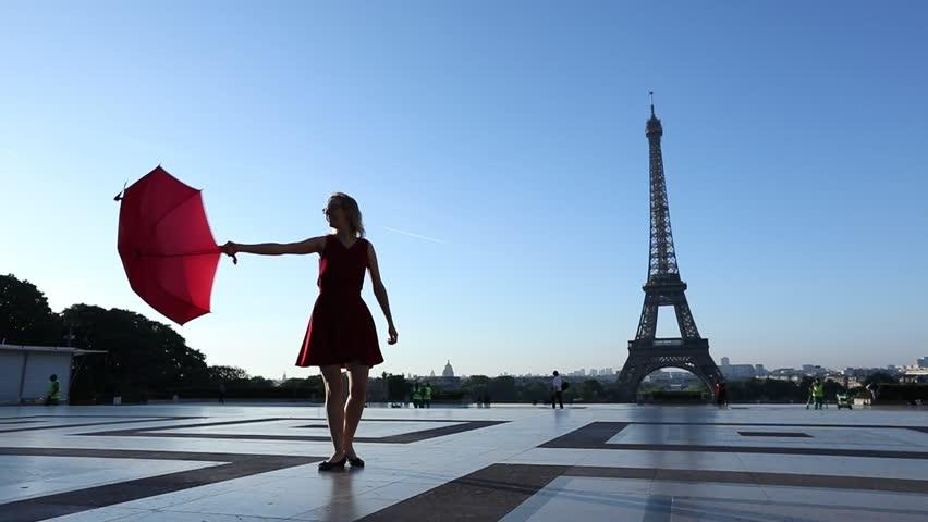 Slow motion of a happy cheerful girl dancing near Eiffel Tower, Paris, France